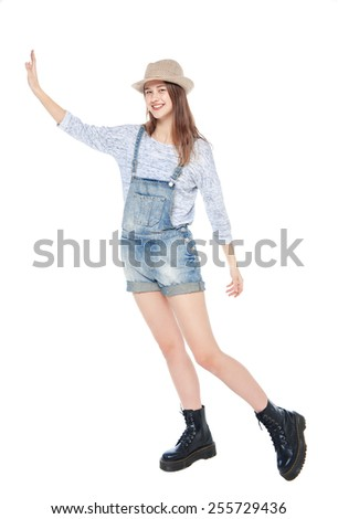 Young fashion girl in jeans overalls pushing something isolated on white background - stock photo