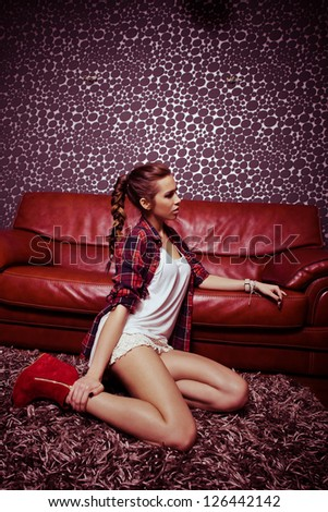 young fashion girl in modern living room sit on carpet lean on leather sofa