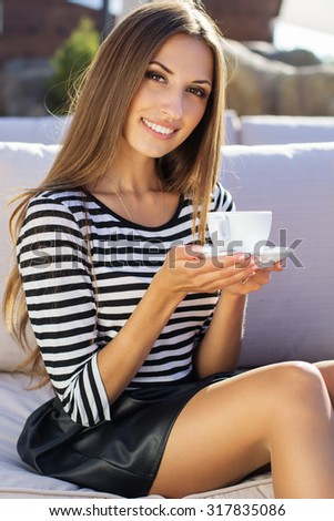 Young fashion girl is resting in a cafe outdoors with cup of coffee. Autumn time