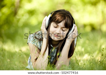 Young fashion girl with headphones at green spring grass.