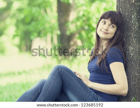 Young fashion girl with headphones at green spring grass. - stock photo
