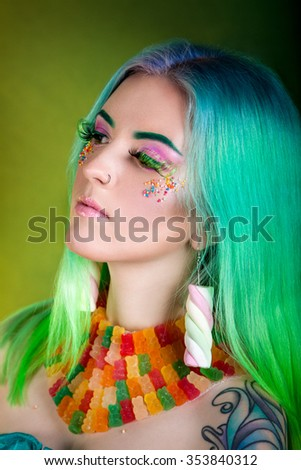 Young fashion glamor girl with colored hair earrings marshmallow, candy makeup and necklace of gelatin bears. Bright style. candy shop - stock photo