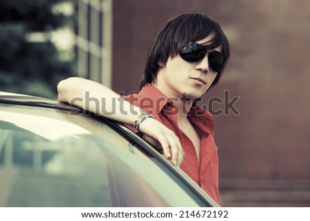 Young fashion handsome man at the convertible car  - stock photo