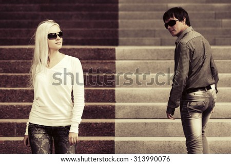 Young fashion man and woman flirting on the steps