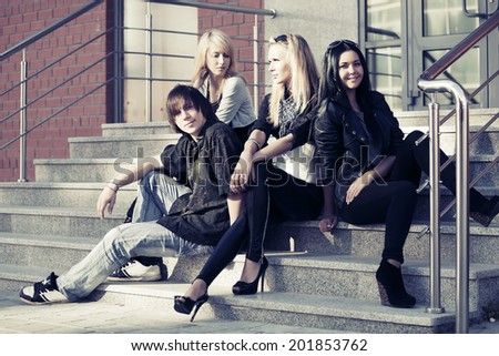 Young fashion man and women sitting on the steps  - stock photo