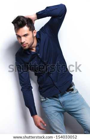 young fashion man passing a hand through his hair while looking at the camera. on a light background - stock photo