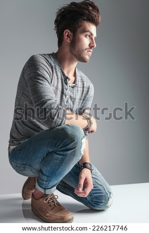 Young fashion man relaxing on one knee while looking away from the camera. On grey studio background. - stock photo