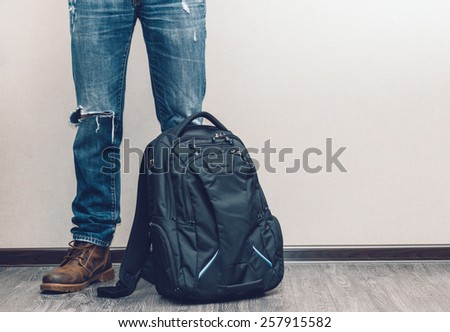 Young fashion man's legs in jeans and boots with backpack on wooden floor - stock photo