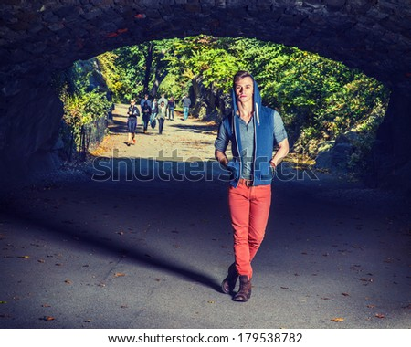 Young fashion man standing under a bridge in a park, dressing in a blue sleeveless hoodie,  a gray shirt, red pants and brown boots, hands putting in pockets.  Instagram X-Pro II Filter Effect.  - stock photo