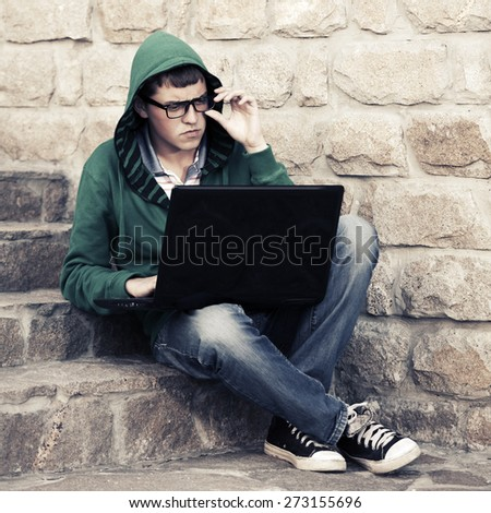 Young fashion man using laptop on the steps - stock photo