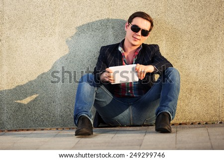 Young fashion man with tablet computer sitting at the wall - stock photo