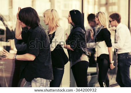 Young fashion men and women looking through mall window  - stock photo