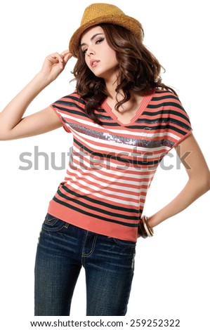 young fashion model in hat posing in studio - stock photo