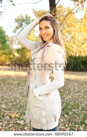young fashion model posing in park in autumn collection
