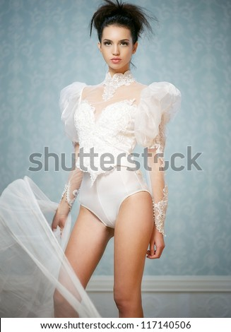 Young fashion model posing in sexy body suit - stock photo