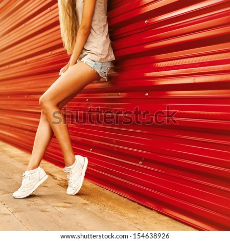 Young fashion outdoor blonde girl posing in sexy style outdoor near red wall. Free copyspace.  - stock photo