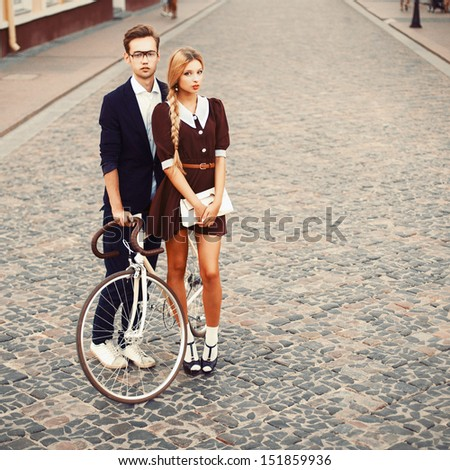 Young fashion pretty couple posing in summer on the street in european town. Handsome man with young girl and retro bicycle - stock photo