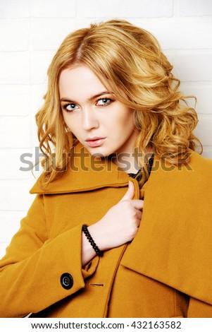 Young fashion woman. Beautiful blonde girl posing in studio in mustard-colored coat. Beauty, fashion. - stock photo
