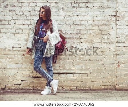 Young fashion woman flirting on the background of old brick wall. Outdoors, lifestyle. - stock photo