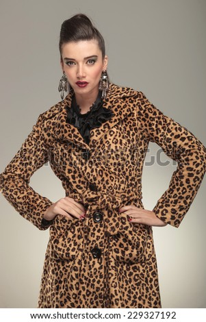 Young fashion woman in animal print coat posing for the camera.