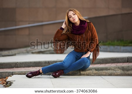 Young fashion woman in leather jacket sitting on city street - stock photo