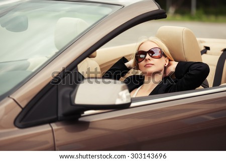 Young fashion woman in sunglasses in a convertible car  - stock photo