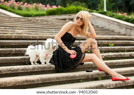 young fashion woman in the park with her dog