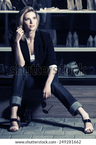 Young fashion woman sitting at the mall window - stock photo