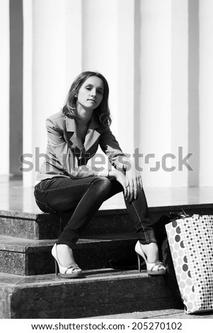 Young fashion woman sitting on the steps after shopping - stock photo