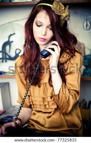 young fashion woman talking on home phone with someone, indoor shot - stock photo
