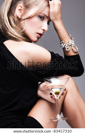 young fashion woman with glass of martini, profile, studio shot - stock photo