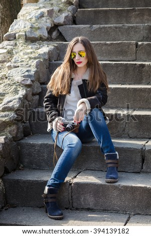 Young fashion woman with photo camera sitting on the stairs. Attractive caucasian girl in city outdoors - stock photo