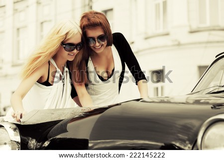 Young fashion women with a road map at the retro car  - stock photo