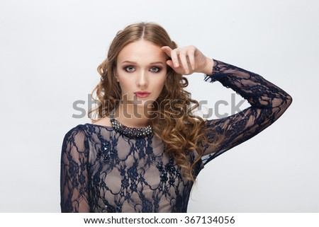 Young fashionable blonde woman in blue dress against white wall with hand gesture