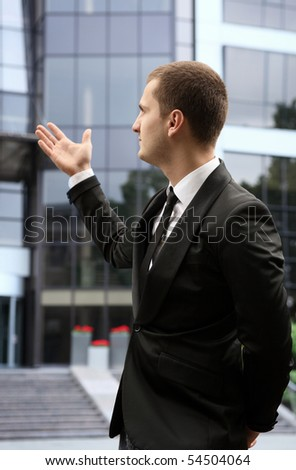 young fashionable businessman showing office building - stock photo