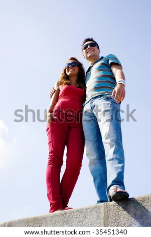 Young fashionable couple against the blue sky.