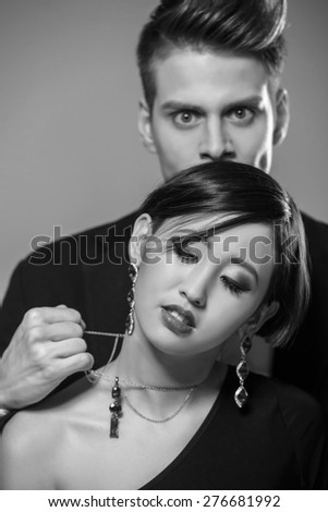 Young fashionable couple dressed in formal clothing posing in the studio. Black and white fashion portrait. Jealousy. - stock photo
