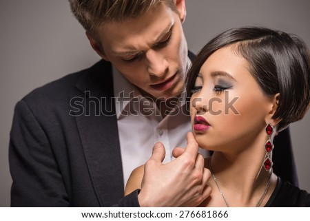 Young fashionable couple dressed in formal clothing posing in the studio on dark background. Fashion portrait. Passion. - stock photo