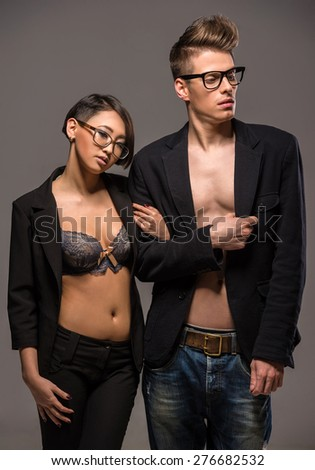 Young fashionable couple in glasses and tuxedos  posing in the studio on dark background. Fashion portrait. - stock photo