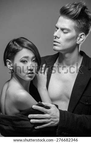 Young fashionable couple in tuxedos  posing in the studio. Black and white fashion portrait. Passion. - stock photo