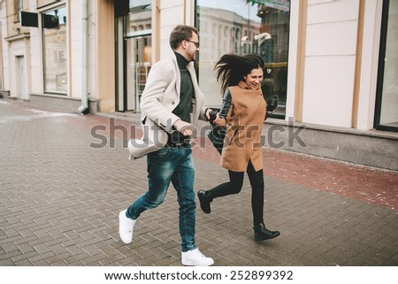 Young fashionable couple walks the city streets in winter hand in hand
