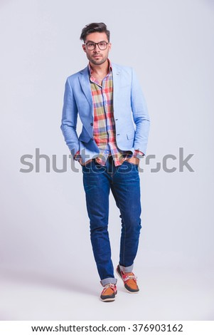 young fashionable guy wearing glasses walking in studio background whit hands in pockets while looking at the camera  - stock photo