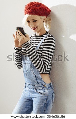 young fashionable lady leaning on a wall and using her smartphone - stock photo