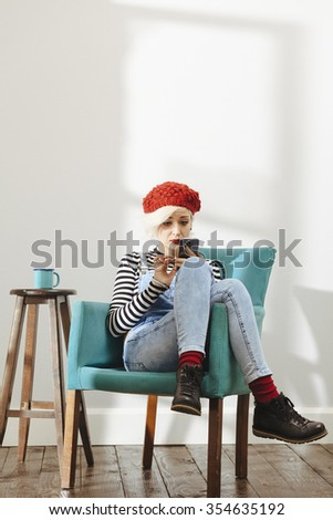 young fashionable lady sitting in an empty room with wooden floor and using her smartphone - stock photo