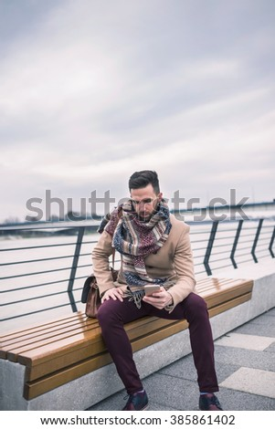 Young fashionable man using phone while sitting in a bench on a rainy day - stock photo