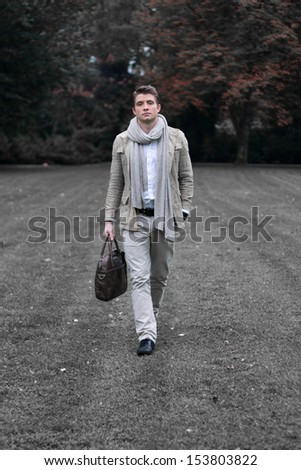Young fashionable man walking at a park in a grey outfit - stock photo