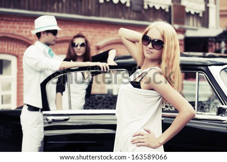 Young fashionable people at the retro car  - stock photo