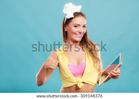 Young fashionable pin up girl using computer tablet browsing surfing the internet. Retro vintage old fashioned woman giving thumb up gesture sign. Fashion and modern technology. - stock photo