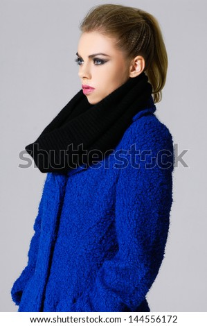 Young fashionable woman wearing blue coat - stock photo