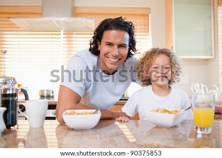 Young father and daughter having cereals in the kitchen together - stock photo